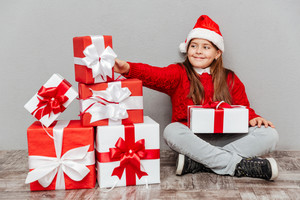 Smiling cute little girl in santa claus hat sitting and taking gift box