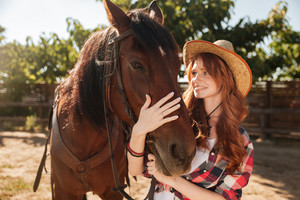 Smiling cute young woman cowgirl taking care and hugging her horse at ranch