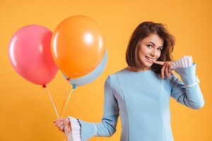 Smiling cute young woman holding colorful balloons over yellow background
