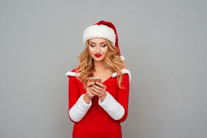 Smiling cute young woman in santa costume with hat using mobile phone