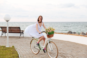 Smiling cute young woman riding bicycle in windy weather on promenade