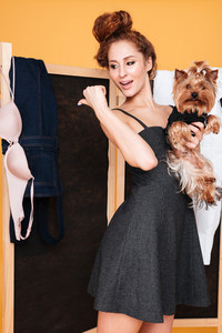 Smiling cute young womna with dog standing near folding screen and pointing away