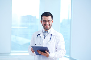 Smiling doctor with clipboard and stethoscope looking at camera