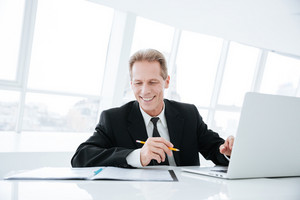 Smiling Elderly business man sitting by the table with laptop and documents in office