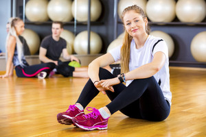 Smiling fit woman in workout outfit at the fitness gym