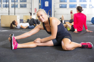 Smiling fit women stretching on the floor