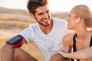 Smiling fitness couple relaxing together after jogging outdoors