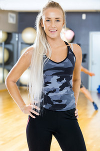 Smiling fitness woman in workout outfit at the gym