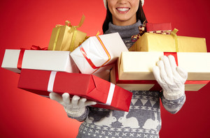 Smiling girl in gloves and pullover holding xmas wrapped gifts