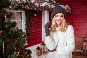 Smiling girl in sweater, hat and mittens near the house