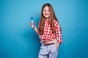 Smiling girl keeping a bottle of water