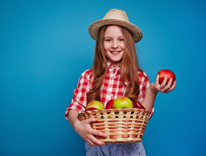Smiling girl keeping fruit basket