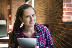 Smiling girl spending time in a cafe using digital tablet
