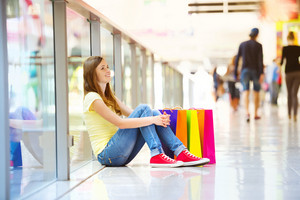 Smiling girl with shopping bags sitting on the floor in shopping mall