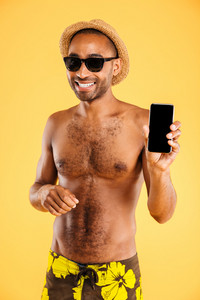 Smiling handsome young african man in hat and sunglasses holding blank screen smartphone over orange background
