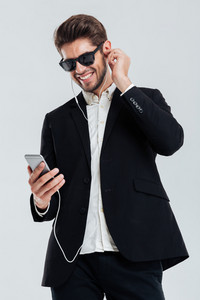 Smiling handsome young businessman listening music with earphones holding smartphone over gray background