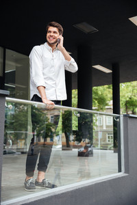 Smiling handsome young businessman standing and talking on cell phone near business center