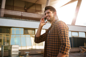 Smiling handsome young man in plaid shirt walking and talking on mobile phone in the city
