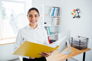 Smiling happy businesswoman sitting on the table with documents in office and looking at camera