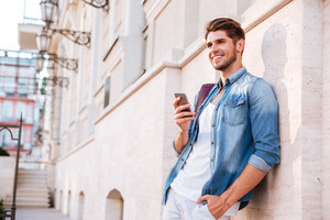 Smiling happy casual man using mobile phone outdoors and leaning on the wall