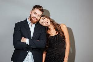Smiling happy couple in smart wear embracing and looking at camera over gray background