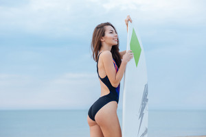 Smiling happy girl with sexy body holding surf board and having fun at the beach