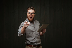 Smiling happy man in eyeglasses holding tablet computer and pointing at camera isolated on a black wooden background