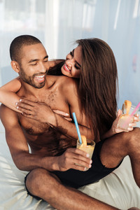Smiling happy multiracial couple sitting on bed and drinking at the beach