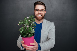 Smiling hipster with flower. close up portrait. looking at camera. isolated black background