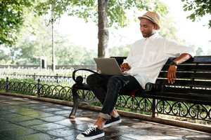 Smiling hipster with laptop in park. with camera. sitting