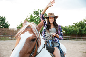Smiling laughing young woman cowgirl riding a horse outdoors