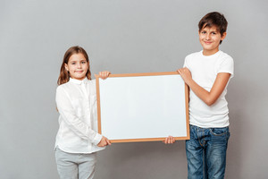 Smiling little boy and girl standing and holding blank white board