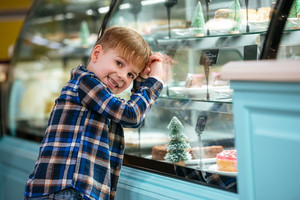 Smiling little boy standing and choosing cake at showcase in cafe