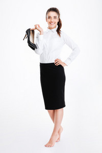 Smiling lovely young businesswoman standing barefoot and holding high heels shoes over white background