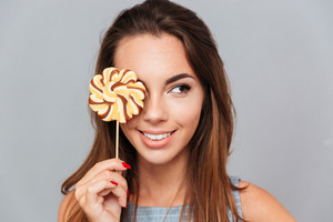Smiling lovely young woman covered her eye with colorful lollipop over grey background