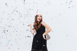 Smiling lovely young woman in santa claus hat holding copyspace on palm over white background