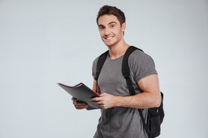Smiling male student standing with folders and backpack over white background