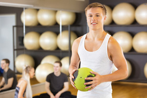 Smiling Man Holding Medicine Ball While Friends Resting In Gym