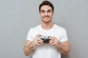 Smiling man holding retro camera in hands and looking at camera. Isolated gray background