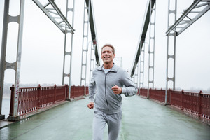 Smiling Man in gray sportswear running on bridge