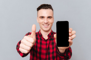 Smiling Man in red shirt showing blank smartphone screen and showing thumbs up. Focus on phone and finger. Isolated gray background