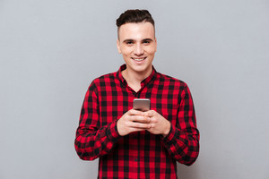 Smiling Man in shirt holding phone in hands and looking at camera. Isolated gray background