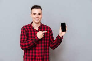 Smiling Man in shirt showing blank smartphone screen and pointing on phone.Isolated gray background