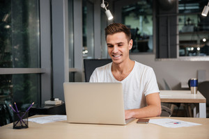 Smiling Man in t-shirt working in office with laptop computer. Coworking