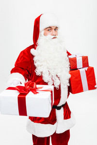 Smiling man santa claus standing and giving present to you