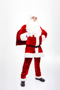Smiling man santa claus standing and holding present sack