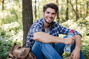 Smiling man sitting in forest looking at camera. guy with water. near the tree and backpack