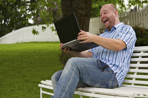 Smiling man / student with his laptop working and celebrate an achievement or a winning in the park. Sitting on a bench.