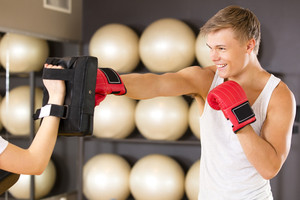 Smiling man training boxing at the fitness gym