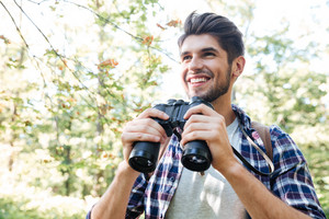 Smiling man with binoculars in forest looking away. from below image. man in shirt
